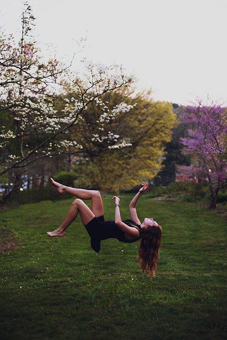 A conceptual portrait of a female model levitating in a garden