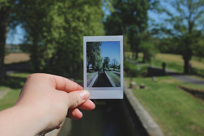 A hand holding a polaroid photo of a landscape withing a landscape
