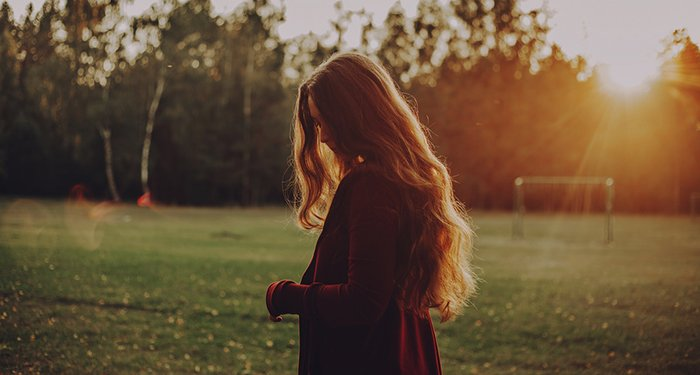 Dreamy portrait of a female model posing in a park during golden hour