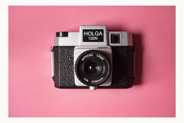 A holga camera on pink background with a white photoshop border