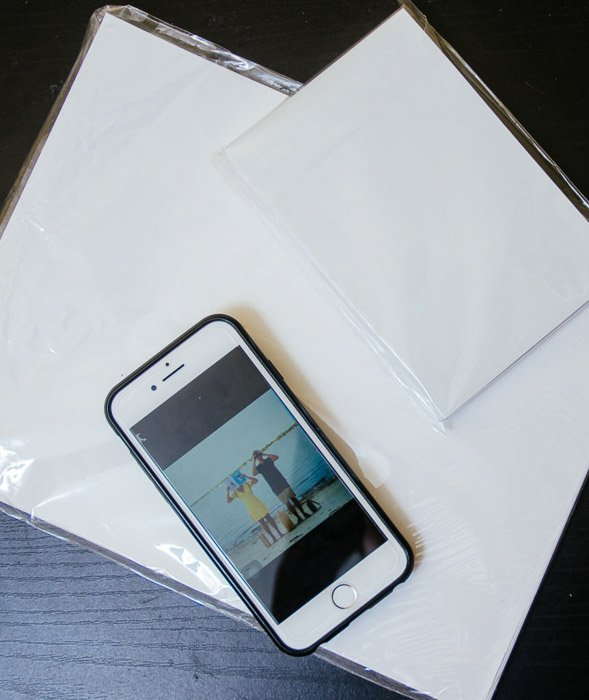 A flat lay photo of an iphone resting on photo paper - print iPhone photos