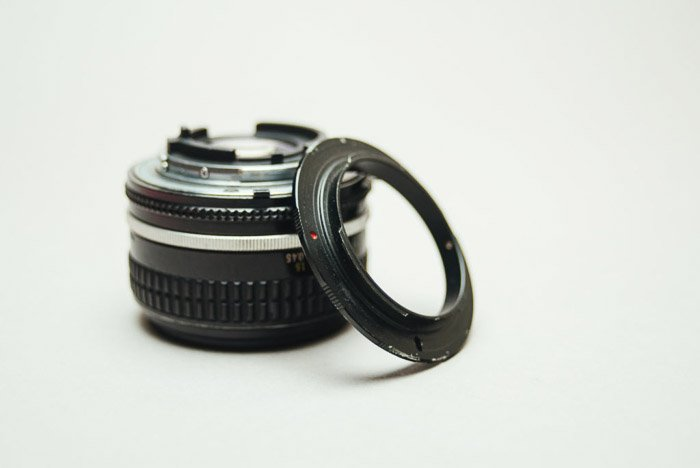 A camera lens beside a reversing ring on white background