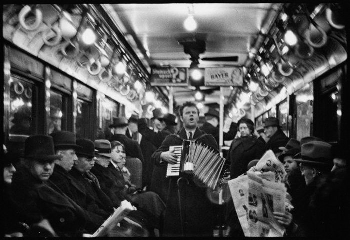 A black and white photo of a musician playing on a train by Walker Evans