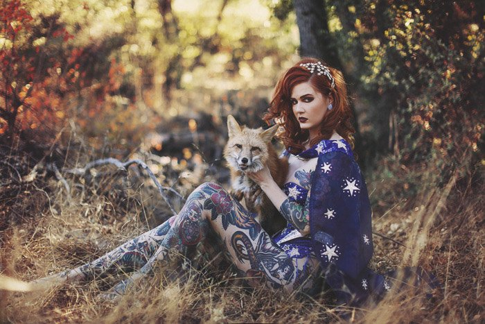 A tattooed female model posing outdoors with a fox