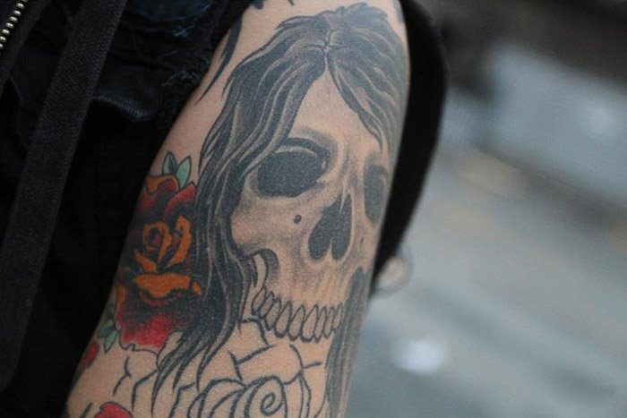 Close up photo of a skull tattoo on a persons upper arm