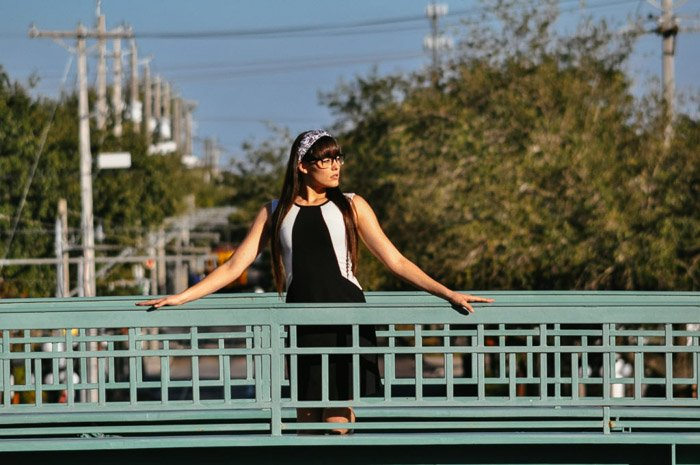 A portrait of a female model posing on a bridge shot with a telephoto lens