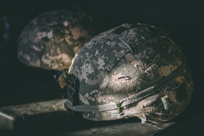 Two army helmets on a shadowy table