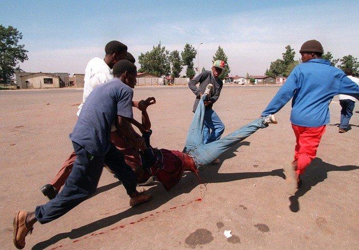 An image of 5 men carrying a bleeding man by war photographer João Silva
