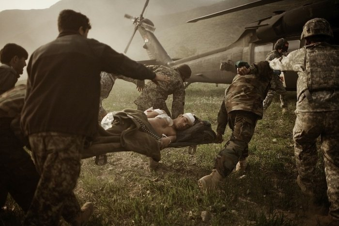 Soldiers helping injured people towards a helicopter by Moises Saman