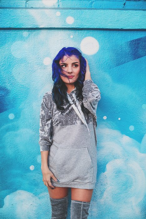 A stock photo of a blue haired female model posing in front of a blue wall