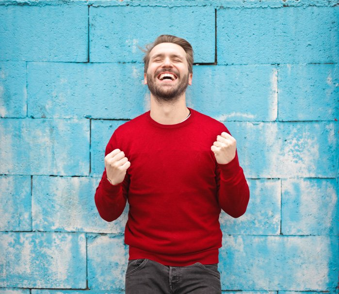A portrait of an overly happy male model posing against a blue wall - bad stock photos