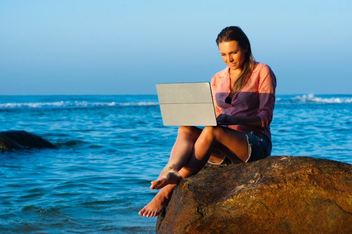 A girl using her laptop while sitting on a rock at the beach - bad stock photos of people