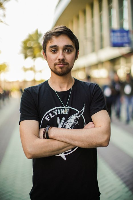 A portrait of a male model posing with folded arms on a street - stock photos of people