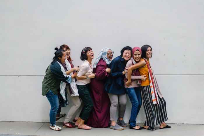 A stock portrait of seven women standing in a conga line pose - bad stock photos