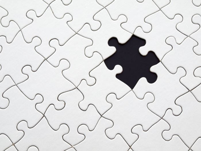 A stock image of a white jigsaw puzzle with one piece missing - stock images