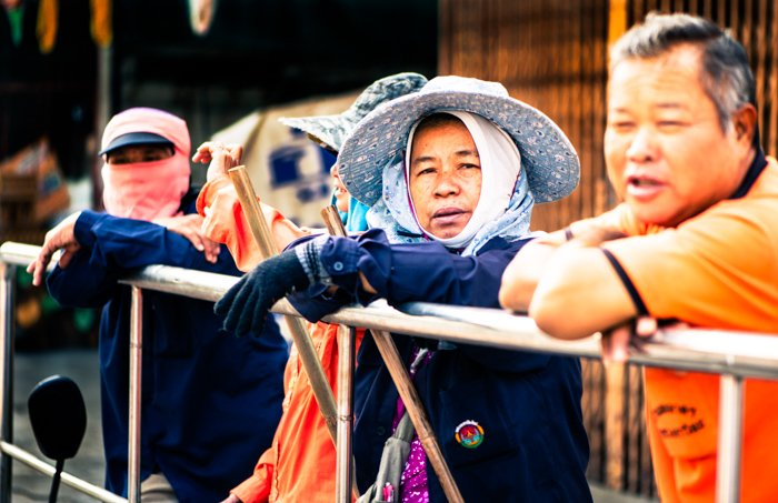 A street portrait of some of the clean up crew waiting behind the floats and participants during the annual flower parade in Chiang Mai, Thailand. Narrative photography tips