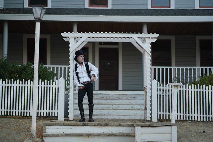 A portrait of a gothic style male model posing in front of a house - photography laws