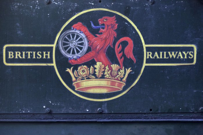 A British railways sign on the side of a steam train.