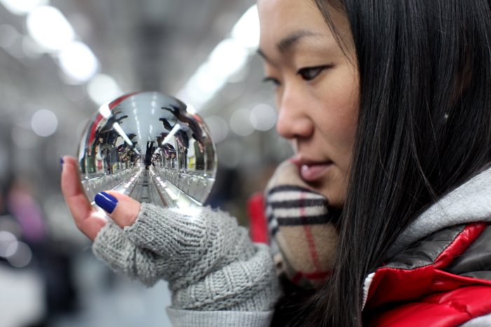 A portarit of a female model holding a crystal ball reflecting the interior of a train