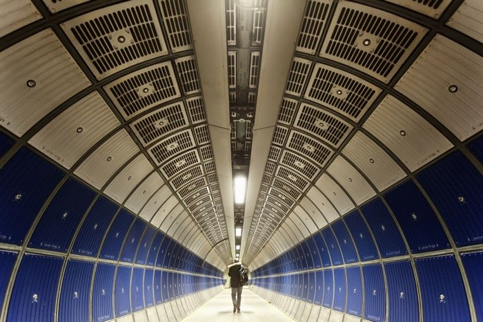 A man walking through a tunnel on jubilee line of the London underground