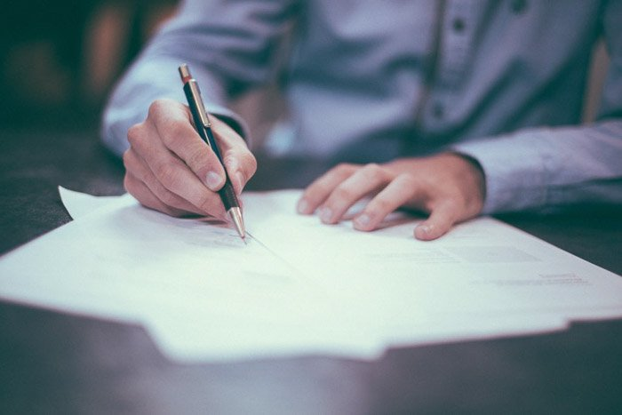 A close up of a person signing a model release form