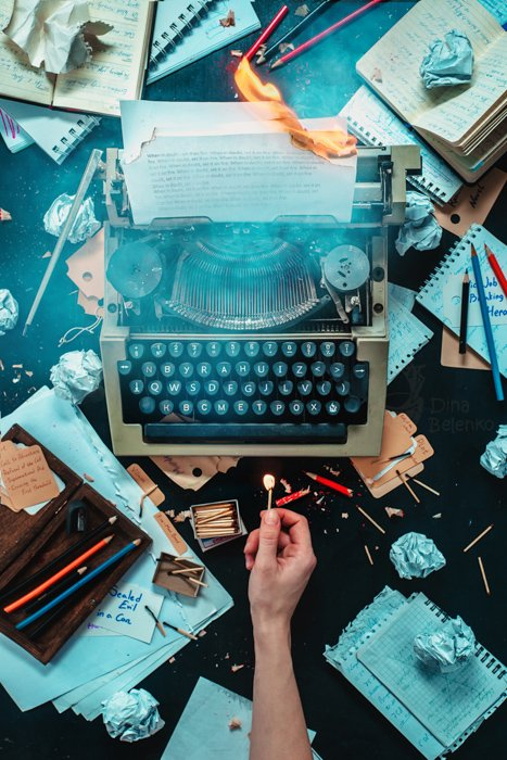 A creative flat lay photo of a messy writing desk and a person holding a match to a typewriter - creative still life photography composition
