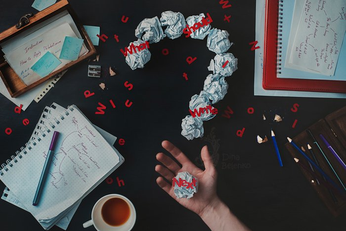 A creative flat lay photo of a messy writing desk and a person holding a crumpled ball of paper with typography overlayed - creative still life photography composition