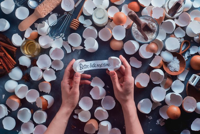A creative still life of many broken eggshells and a persons hands holding a note reading 'better luck next time' - text in photography