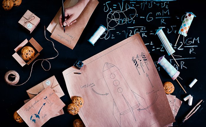 A creative still life image featuring paper, blueprints, cookies and stationary - examples of using text in photography