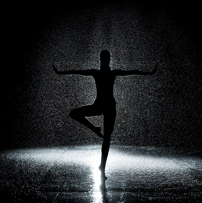 Artistic ballet photography shot of the silhouette of a female ballerina dancing onstage in low light