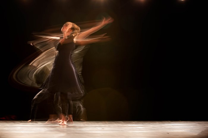 An artistic blurry portrait of a ballet dancer onstage - ballet photography tips