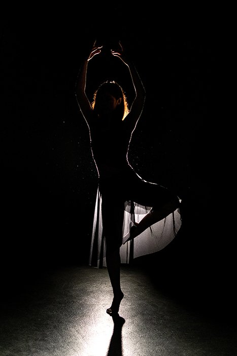 A beautiful ballet photography shot of a female dancer posing onstage in low light