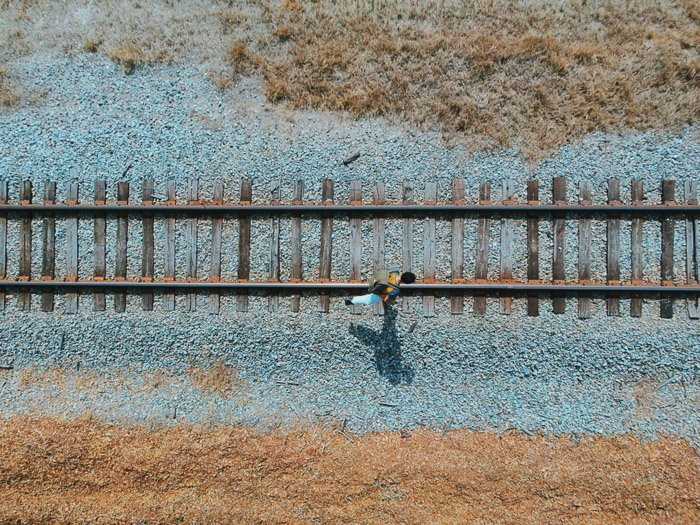 A birds eye view camera angle of a man walking along traintracks