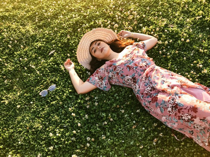 A portrait of a female model lying down outdoors shot from high camera angles