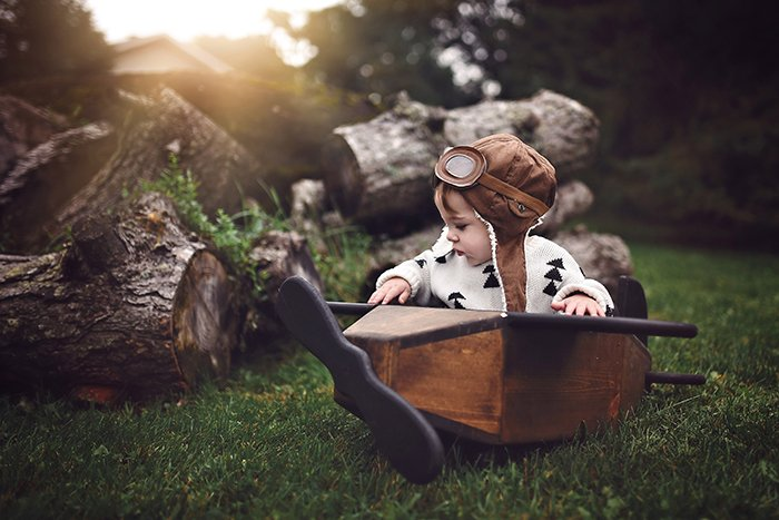 A conceptual photo of a young boy in a wooden boat outdoors