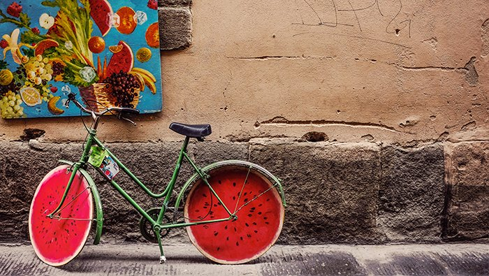 A street photo of a bicycle with watermelon painted wheels - conceptual photography ideas