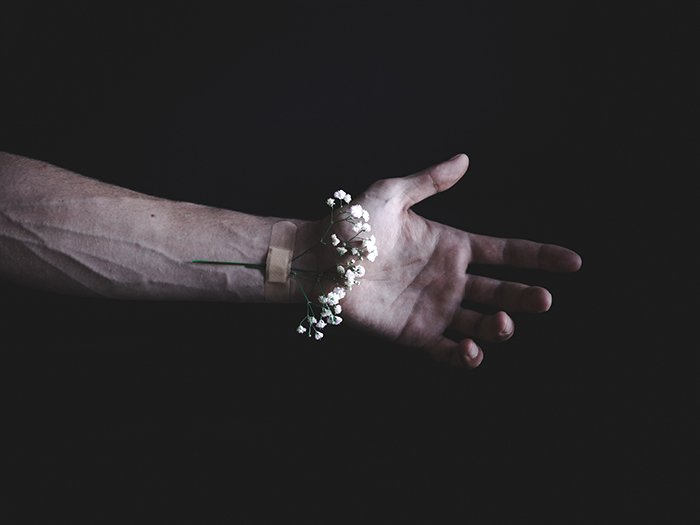 A dark and moody conceptual photo of a flower bandaged to a persons wrist