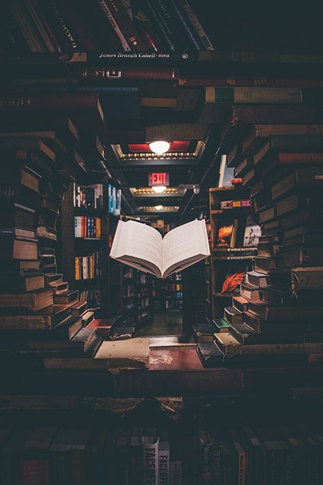 A conceptual photo of a book levitating in a library
