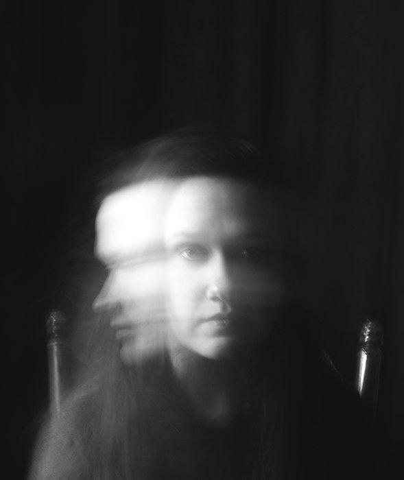 A surreal monotone portrait of a female model featuring motion blur - conceptual photography ideas