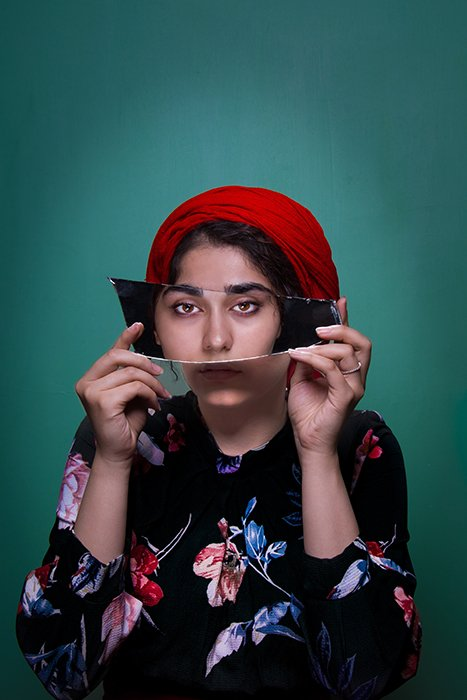 A colorful portrait of a female model holding a mirror to her face - conceptual photography ideas