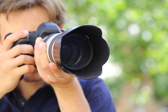 A photographer taking a shot with a DSLR camera - understanding different camera parts