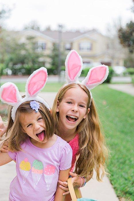 Sweet easter portrait photo of two little girls in bunny ears posing outdoors