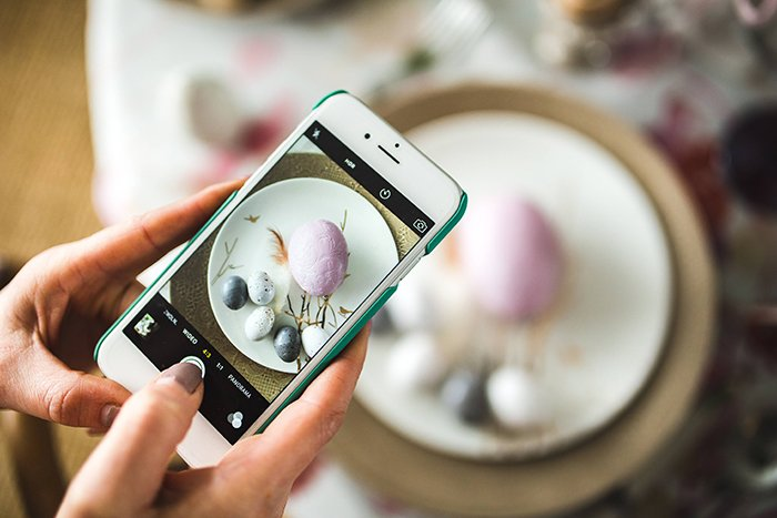 A close up of a person shooting an Easter still life photo with a smartphone