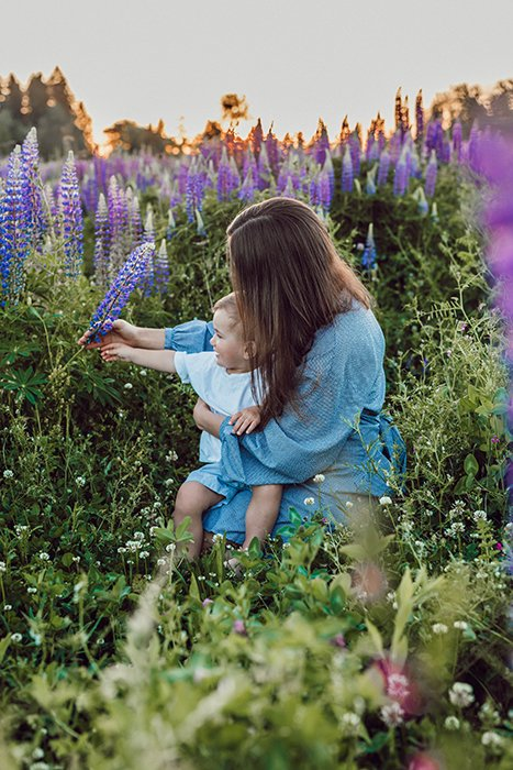 A cosy portrait of a mother and baby posing among wild flowers - family easter picture ideas