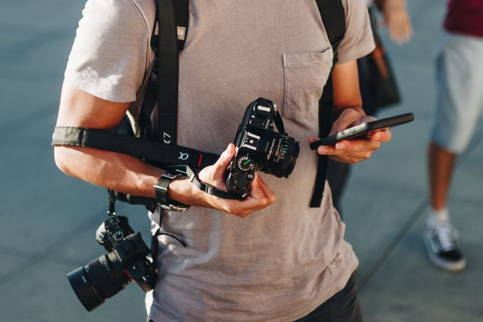 an image of a street photographer holding a 35mm film camera