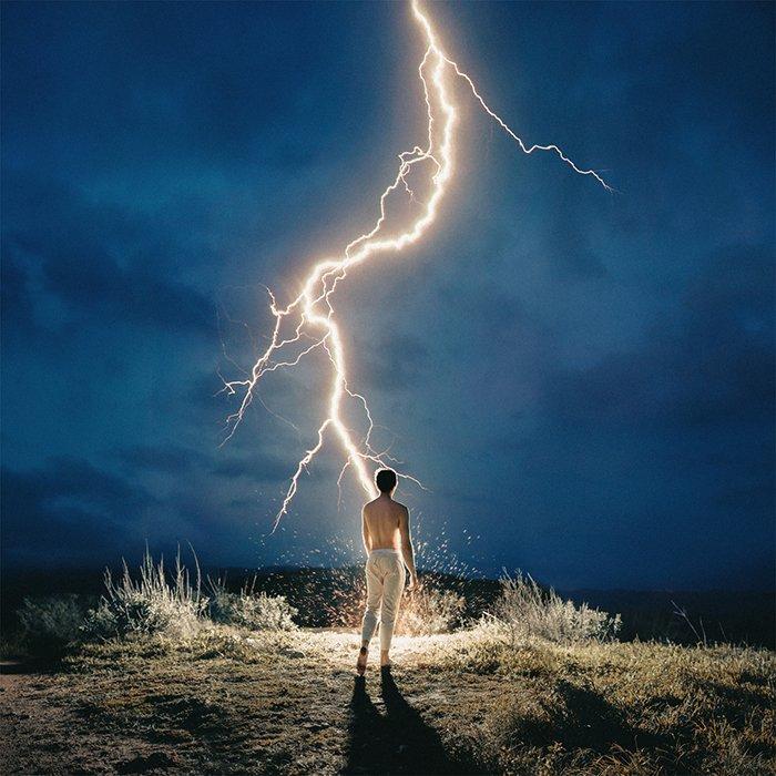 An impressive portrait of a man standing under a lightning bolt by fine art photographer Alex Stoddard
