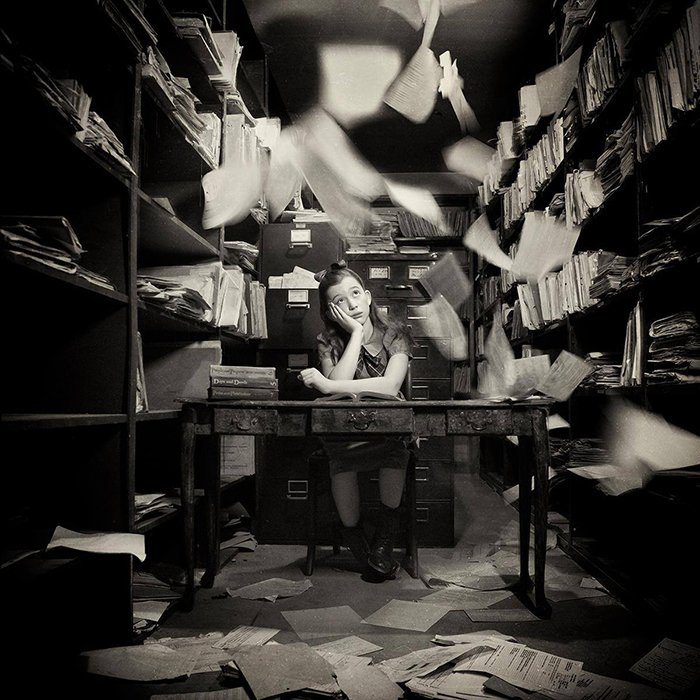 Conceptual black and white portrait of a young girl sitting in an office with papers flying around by fine art photographer Carolyn Hampton