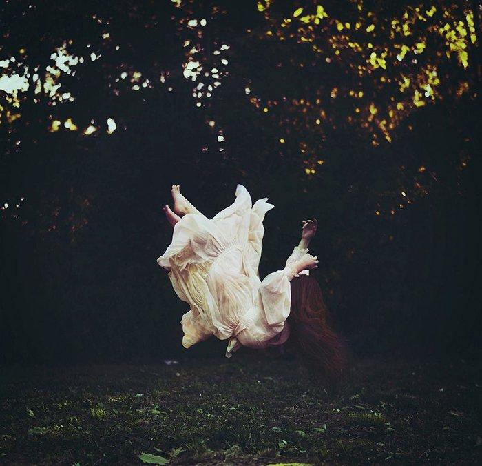 Surreal fine art portrait of a female model falling outdoors