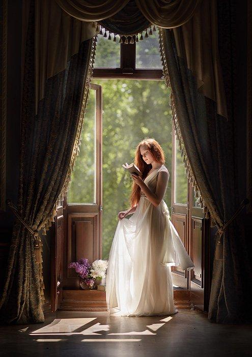 A dreamy fine art photography portrait of a female model reading at a windowsill by fine art photographer Olga Fler