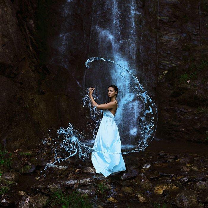 Artistic portrait of a female model posing under a waterfall by Sarah Ann Loreth